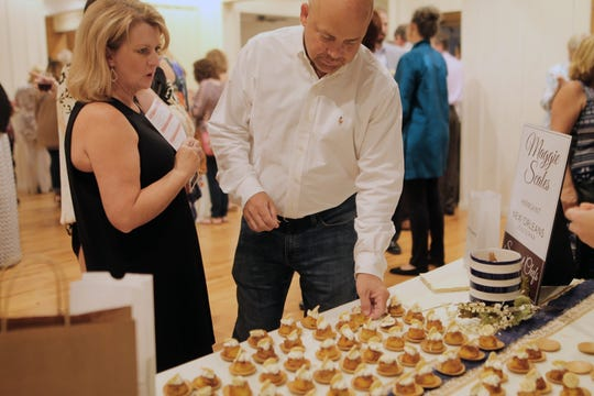 Attendees at Sweetest Chefs of the South pause to try the fare at the Maggie Seales of New Olreans table.