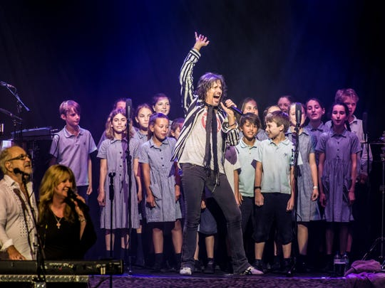 Foreigner vocalist Kelly Hansen is backed by a group of children during a performance for Foreigner's Europe 2016 tour.