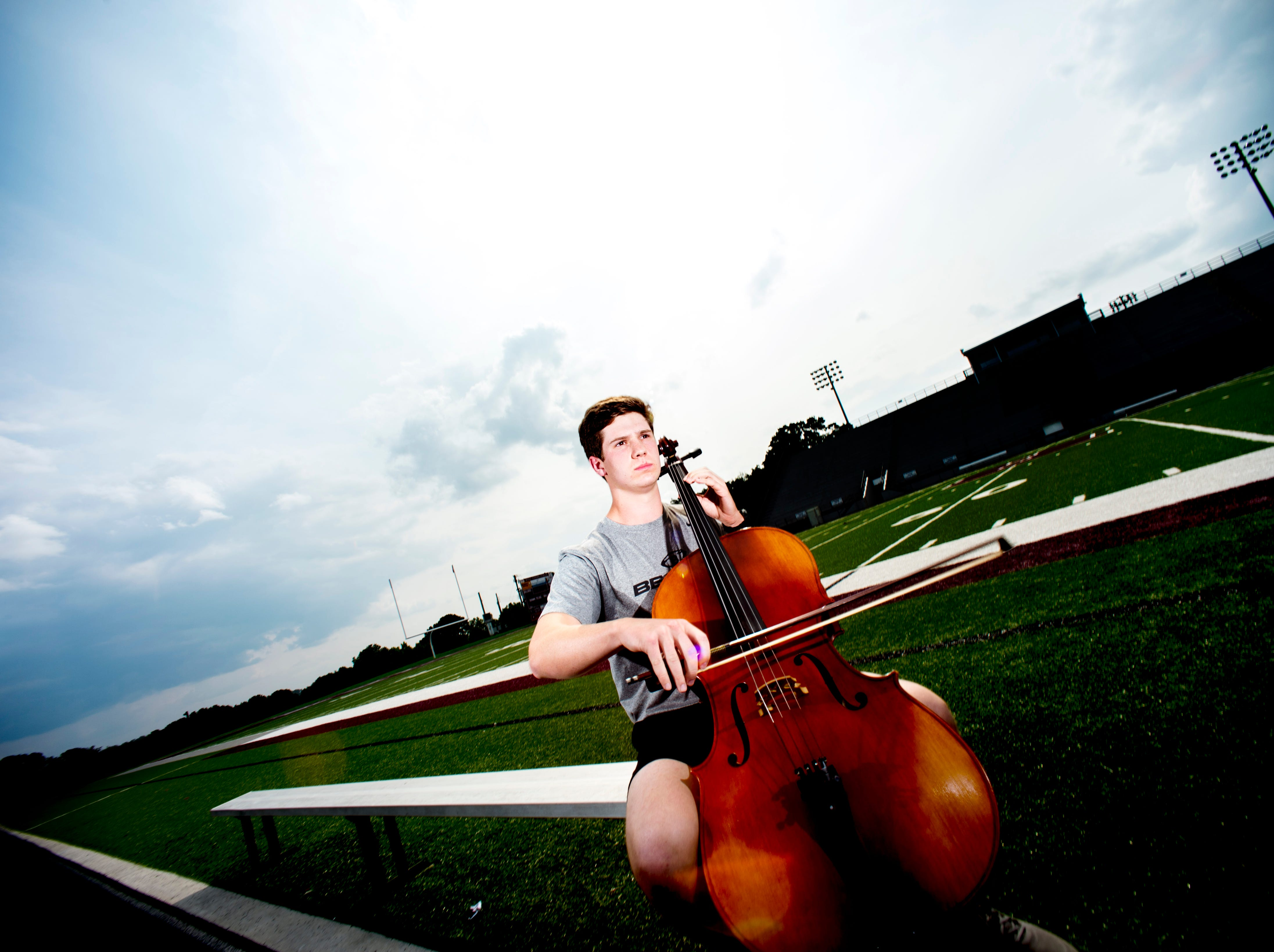Bearden senior linebacker and orchestra member Mac Chandler plays his cello on the football field at Bearden High School in Knoxville, Tennessee on Wednesday, August 22, 2018.