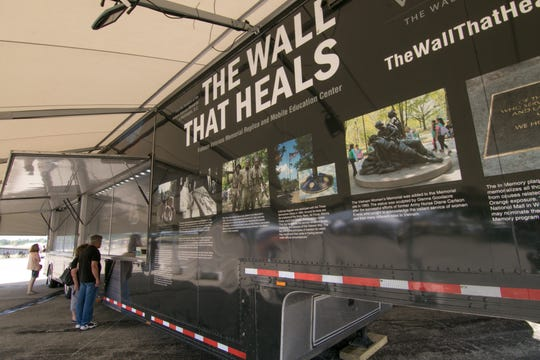 The vehicle used to transport The Wall That Heals, shown Thursday, Aug. 23, 2018, converts to a mobile education unit. Shown here are some of the memorials paying tribute to those who served in the Vietnam War.