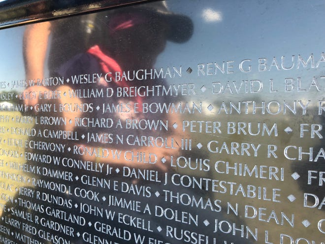 Barbara Brum is reflected on The Wall That Heals as she looks at the name of her son, Peter Brum, who was killed 50 years ago while serving in the Vietnam War.  The Wall That Heals exhibit is at the Spencer J. Hardy Airport in Howell through Aug. 26.