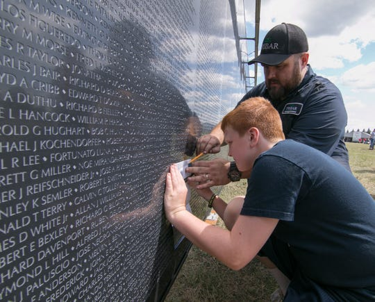 Robby Green and his son R.J. make a rubbing of the elder Green's great uncle, Sammy Lee Bedwell, Thursday, Aug. 23, 2018 at The Wall That Heals.