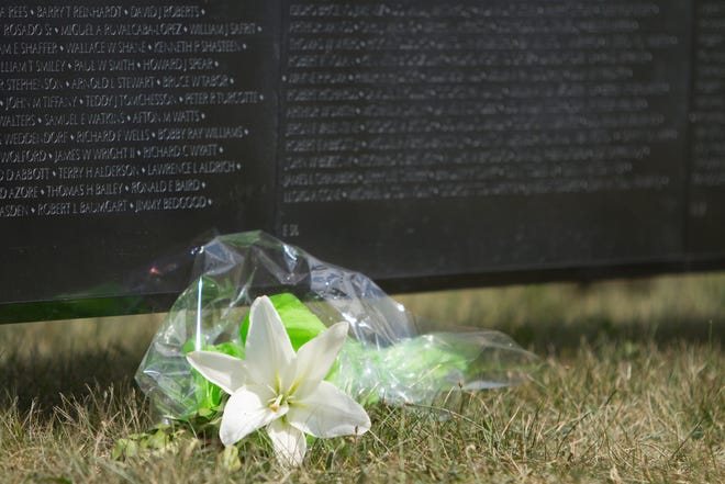 A floral bouquet is left on the ground at the base of The Wall That Heals exhibit.