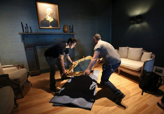 Vincent Moloney, left, and John Witzke carefully placed a mirror on a mat before hanging it at the Frazier Kentucky History Museum.  They are putting the finishing touches on the Gracious Room as they prepare to unveil the official starting point for the Kentucky Bourbon Trail.