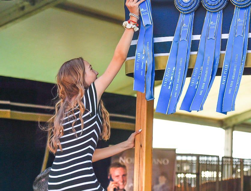 Ella Herrin gets a lift from her Dad, Charles Herrin to her sister, Logan Herrin's blue ribbon