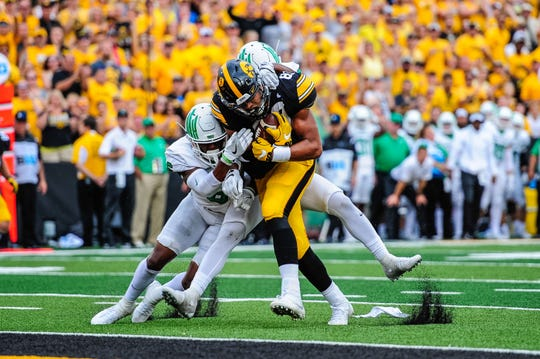 Iowa Hawkeyes tight end Noah Fant (87) scores a touchdown reception as North Texas Mean Green safety Kishawn McClain (6) and safety Khairi Muhammad (4) go for the tackle during the third quarter at Kinnick Stadium.