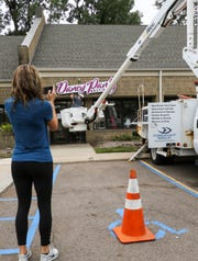Megan Villasurda, owner of Dancy Pantz Boutique in Okemos takes a photo of signage being hung on her new storefront, Thursday, Aug. 16, 2018.