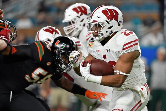 Wisconsin Badgers running back Jonathan Taylor (23) runs the ball against the Miami Hurricanes during the first half in the 2017 Orange Bowl at Hard Rock Stadium.