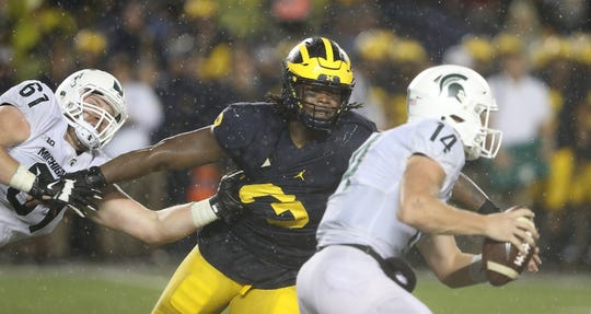 Rashan Gary of the Michigan Wolverines makes the stop on Brian Lewerke of the Michigan State Spartans during the fourth quarter of the game at Michigan Stadium on October 7, 2017 in Ann Arbor, Michigan. Michigan State defeated Michigan 14-10.