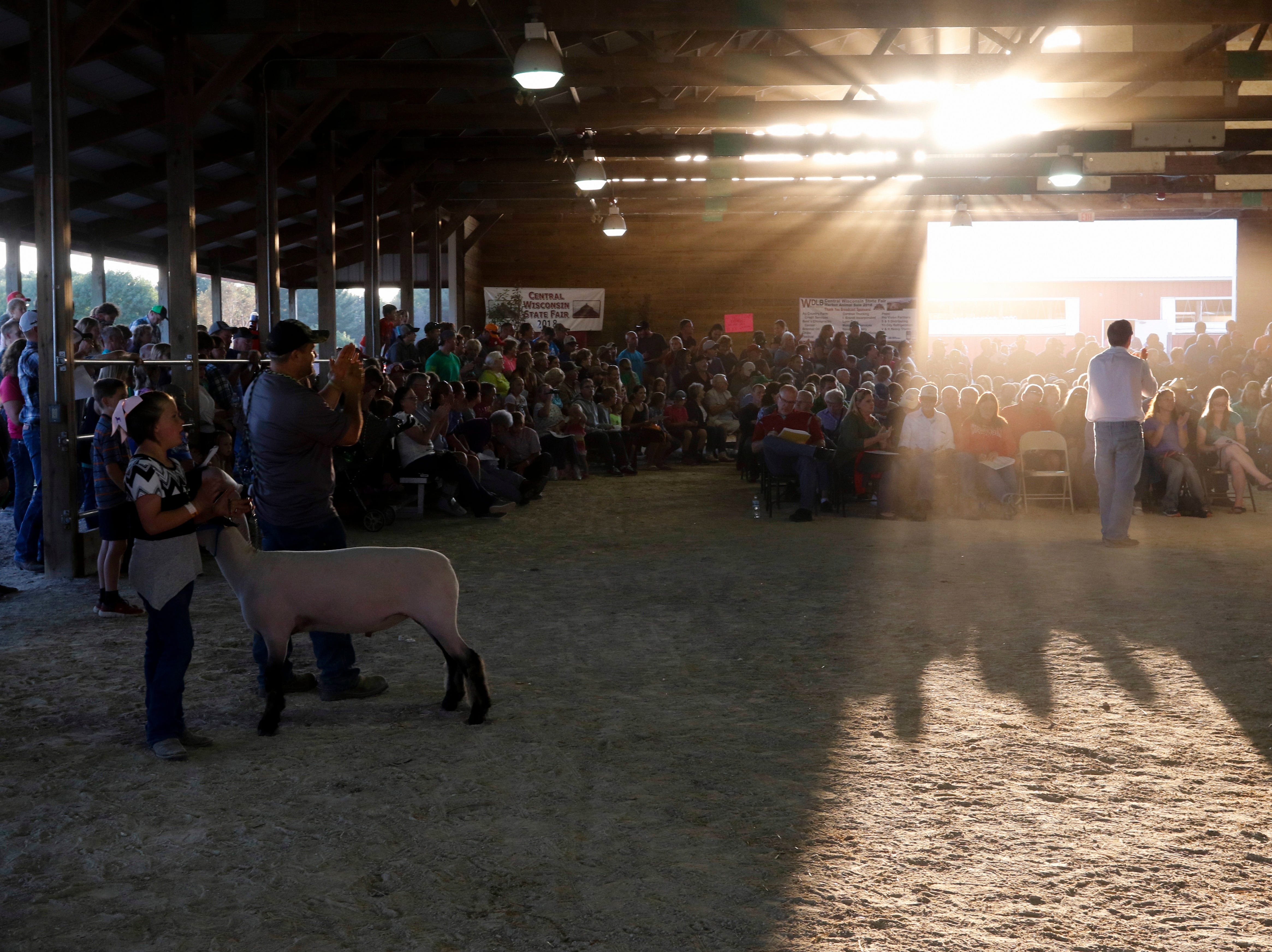 Chris Ignatowski of Iggy's Auction, right, takes bids during the market animal sale at the Central Wisconsin State Fair in Marshfield Wednesday, August 22, 2018.