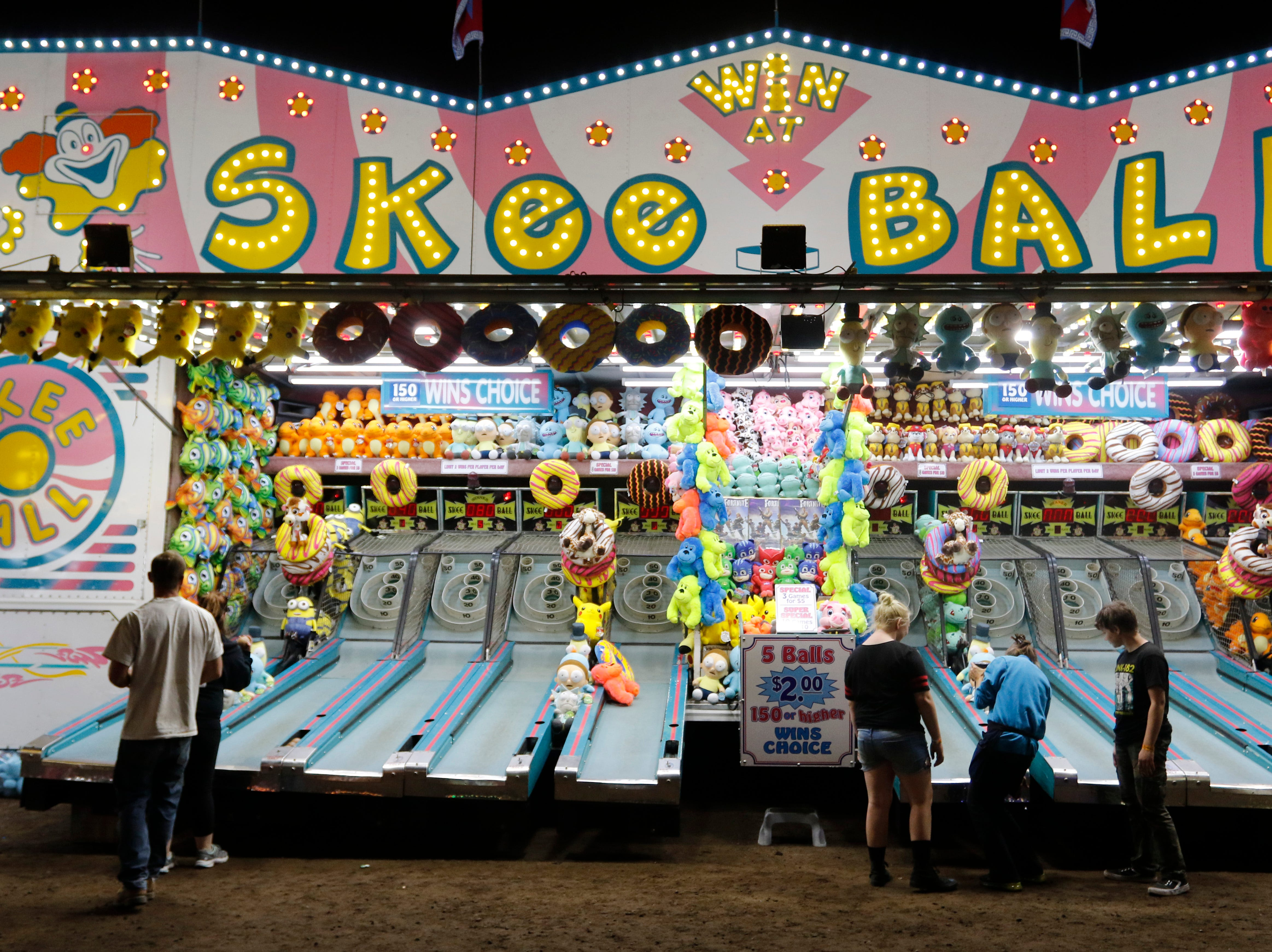 Fairgoers take a shot at the skee ball game at the Central Wisconsin State Fair in Marshfield Wednesday, August 22, 2018.