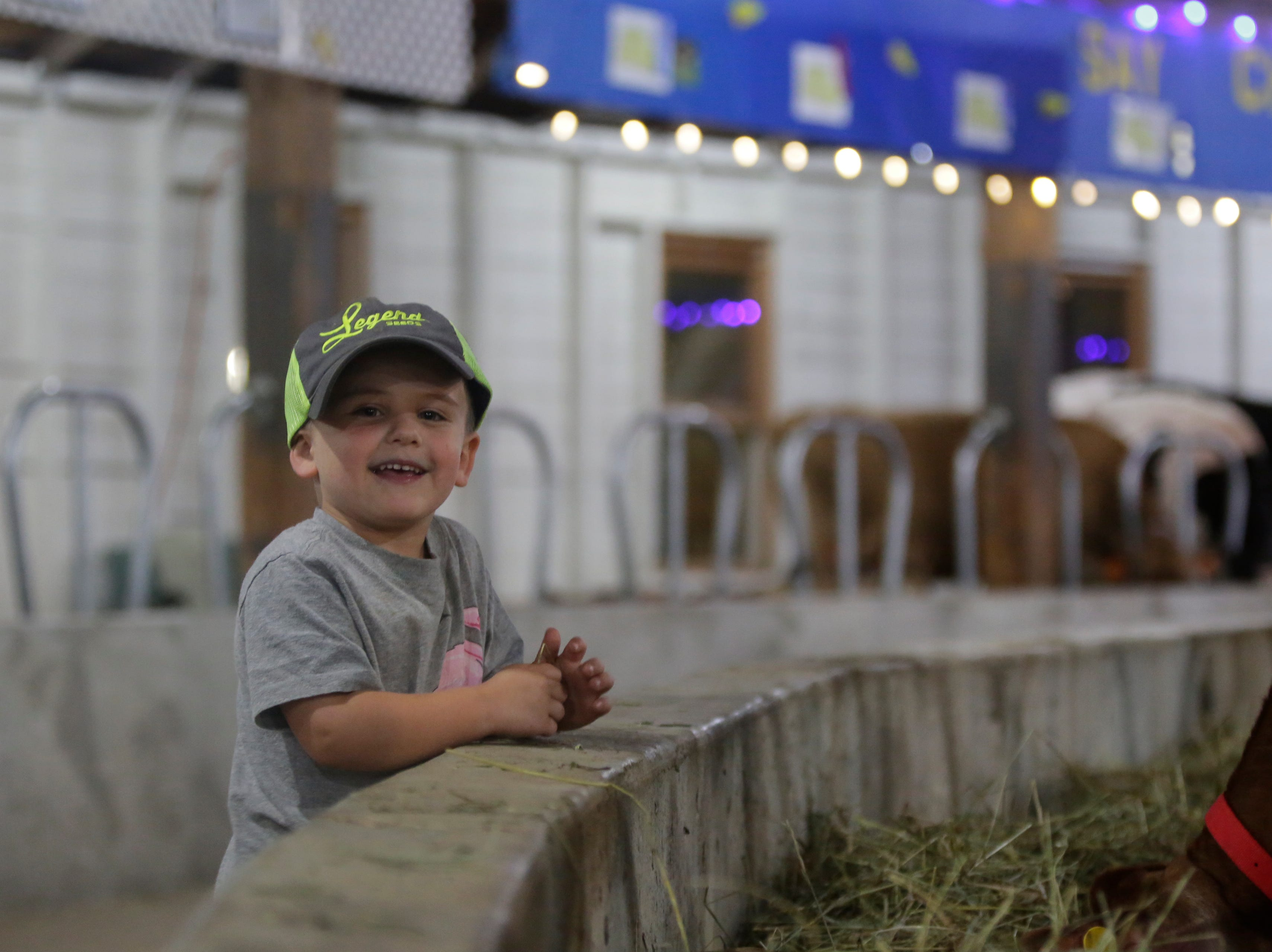 Ryker Breu, 4, smiles while visiting with some cows in the world's largest round barn at the Central Wisconsin State Fair in Marshfield Wednesday, August 22, 2018.