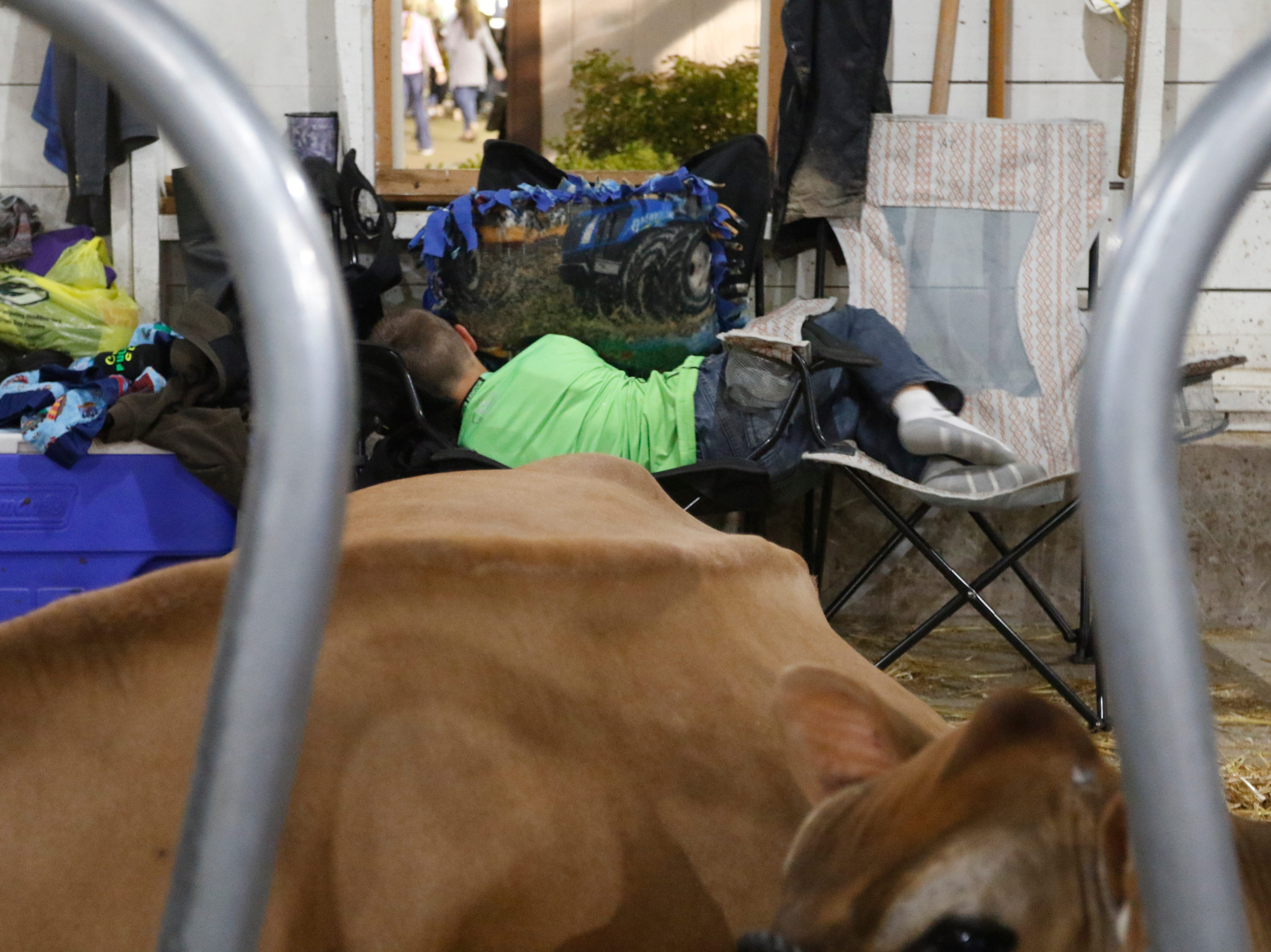 Carter Trowbridge, 10, tries to take a nap between two folding chairs in the world's largeste round barn during the Central Wisconsin State Fair in Marshfield Wednesday, August 22, 2018.