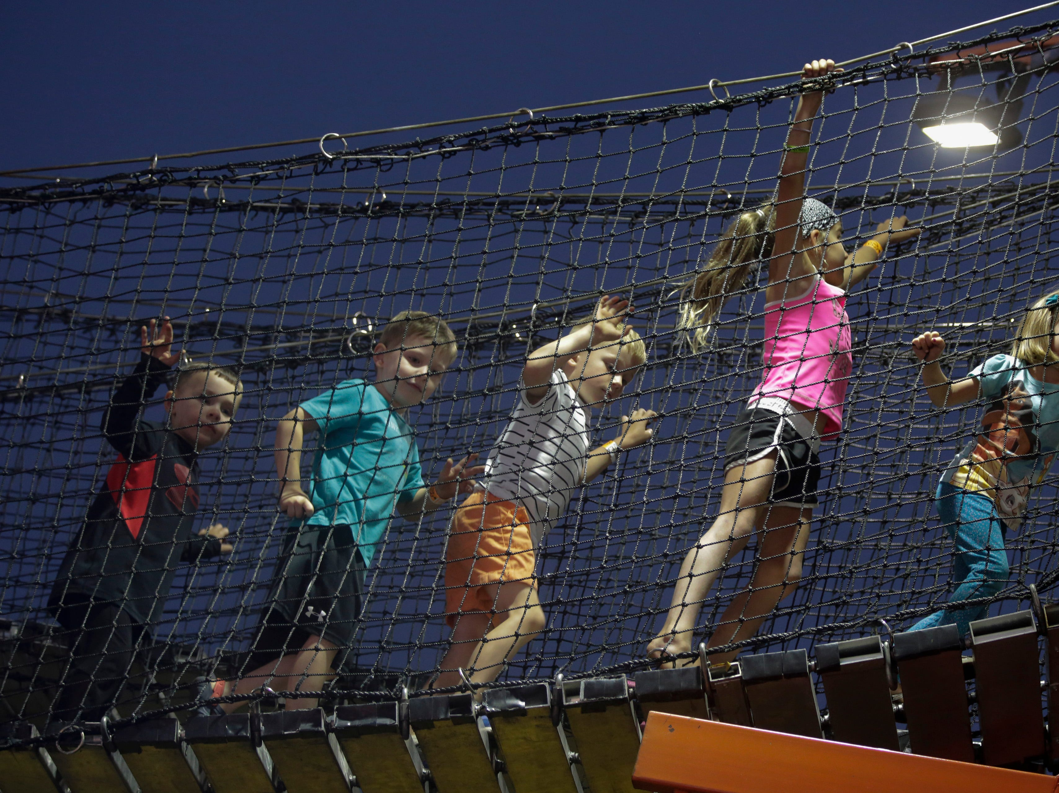 A group of kids walk across the rope bridge on a fun house at the Central Wisconsin State Fair in Marshfield Wednesday, August 22, 2018.