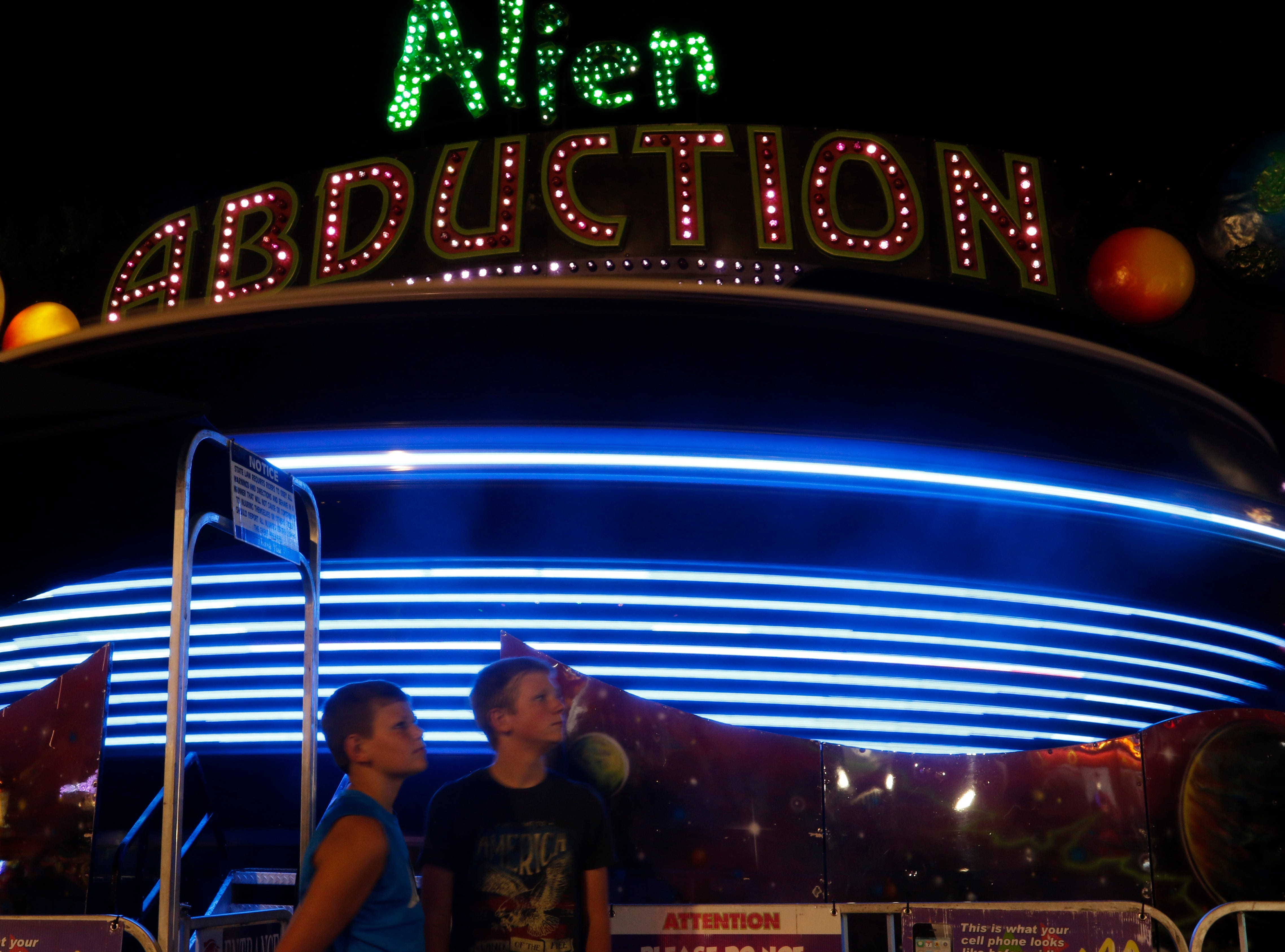 Seth Roewe, 12, left and Caleb Grambsch, 12, wait to ride the alien abduction at the Central Wisconsin State Fair in Marshfield Wednesday, August 22, 2018.