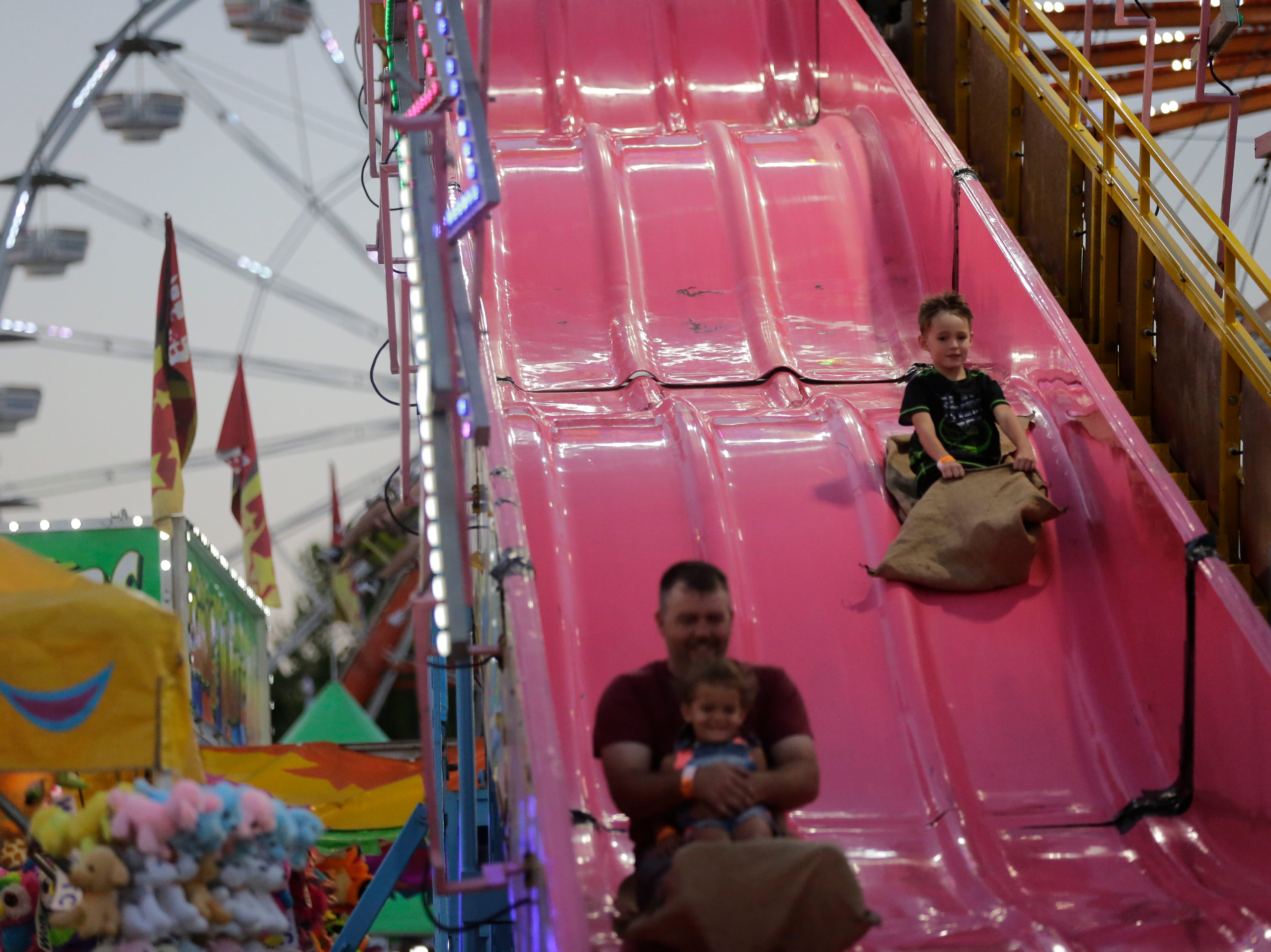 Kenneth, left, Raina, 3, and Ryder Collopy, 6, right, go down the big slide at the Central Wisconsin State Fair in Marshfield Wednesday, August 22, 2018.