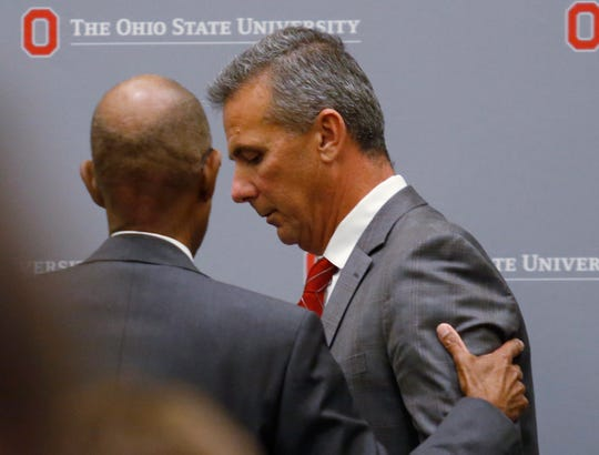 Ohio State president Michael Drake offers words to football coach Urban Meyer as they leave the stage following Wednesday's news conference.
