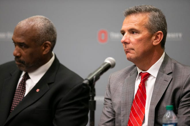 Ohio State head football coach Urban Meyer and athletic director Gene Smith listen as university president Michael Drake addresses the media on Wednesday night.