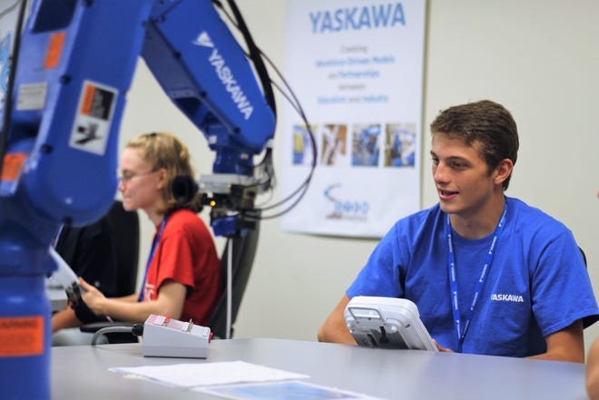 Riley McElroy, a senor at Tri-Rivers Career Center interacts with a Yaskawa robot on Thursday. Students like McElroy will have the opportunity to work with more sophisticated equipment as the career center's RAMTEC program partners up with companies like  Yaskawa Motoman and Whirlpool to develop a more advanced robotic program.