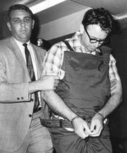 Sheriff William N. Morris Jr., escorts James Earl Ray into the Shelby County Jail in Memphis before dawn July 19, 1968. Ray, who was protected by a bulletproof apron, had been extradited from London.  This photo, originally an uncredited handout from the Shelby County Sheriff's Department, was shot by Gil Michael.