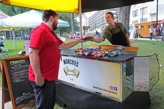 Aidan Benkowski, one of the owners of the Munchies food cart, hands a sandwich to a customer during the Westown Farmers Market, held 10 a.m. to 2 p.m. Wednesdays through Oct. 31 at Zeidler Union Square, N. 3rd and W. Michigan streets.