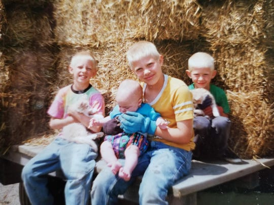 As a boy, Nathan Zwagerman, wearing blue gloves, posed with bales of straw at the family farm in western Michigan along with his brothers Mike (from left), Jacob and Luke.