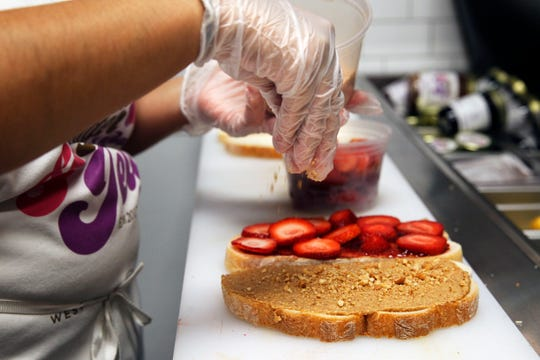 Selina Domenech makes the Strawberry Lovers sandwich at the Peanut Butter & Jelly Deli.
