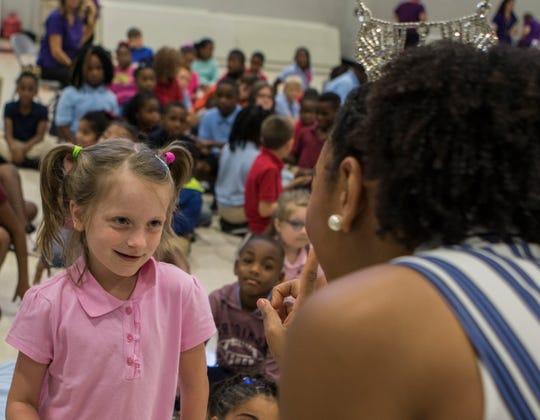 """Rachel Dunn, 6, shyly smiles at 2018 Miss Louisiana Holli' Conway during Conway's visit to her former grade school Lakeshore Elementary in Monroe, La. Conway wanted to visit the school to encourage the children that they shouldn't give up on their dreams. """"It's like coming back home,"""" Conway said about her visit to the school where she was once a student."""