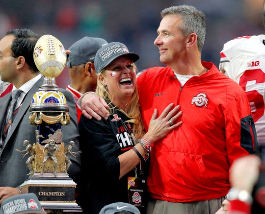 FILE - In this Jan. 1, 2016, file photo, Ohio State head coach Urban Meyer hugs his wife, Shelley, after their 44-28 win over Notre Dame in the Fiesta Bowl NCAA college football game, in Glendale, Ariz. Ohio State placed Meyer on paid administrative leave Wednesday, Aug. 1, 2018, while it investigates claims that his wife knew about allegations of abuse against former Buckeyes assistant Zach Smith, who was fired.