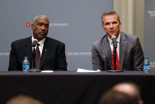 Ohio State football coach Urban Meyer, right, answers questions as athletic director Gene Smith listens during a news conference in Columbus, Ohio, Wednesday, Aug. 22, 2018. Ohio State suspended Meyer on Wednesday for three games for mishandling domestic violence accusations, punishing one of the sport's most prominent leaders for keeping an assistant on staff for several years after the coach's wife accused him of abuse. Athletic director Smith was suspended from Aug. 31 through Sept. 16.  (AP Photo/Paul Vernon)
