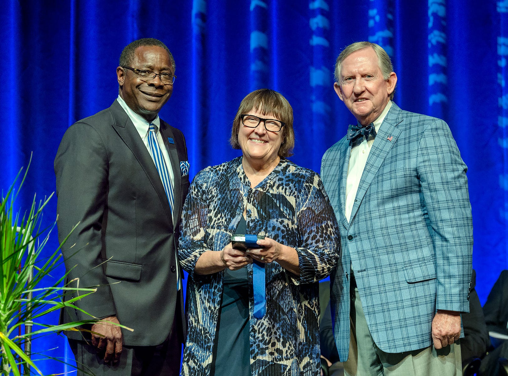 Judith Iriarte-Gross, a professor of chemistry at MTSU since 1996, center, receives the MTSU Foundation's Career Achievement Award during the 2018 Fall Faculty Meeting held Thursday, Aug. 23, inside Tucker Theatre. Shown with her are MTSU President Sidney A. McPhee, left, and Ron Nichols, president of the MTSU Foundation Board and an alumnus.