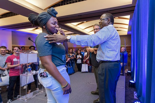 True Blue Tour guest Christan Lee, a student at Centennial High School in Williamson County, reacts with emotion after receiving a $2,500 scholarship to MTSU from Provost Mark Byrnes, center, and MTSU President Sidney A. McPhee.