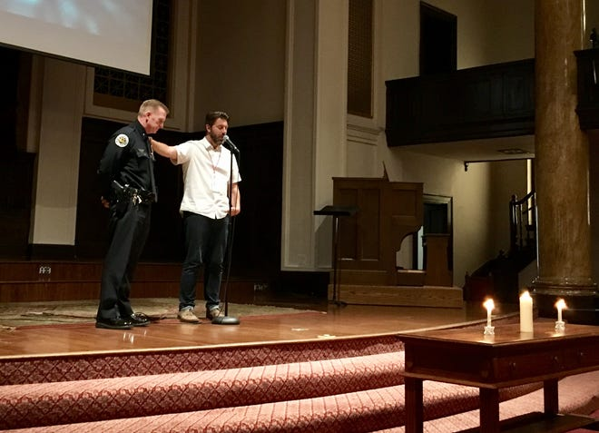 Pastor Jason Rumbough prays for Metro Nashville Police Commander David Imhof and other officers on Wednesday at Eastland Baptist Church.