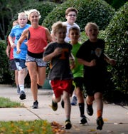 Certified running coach Mandy Oakes, third from left, trains a group of boys on Wednesday, August 22, 2018, in Franklin, Tenn., as they prepare to complete in the Franklin Classic.