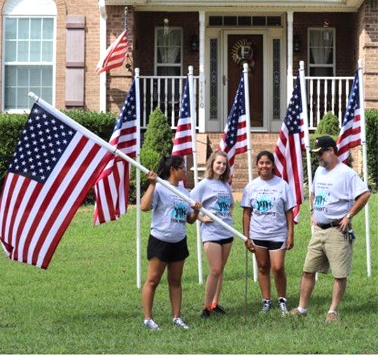 Fairview High Band representatives ready to place U.S. flags for Labor Day (l-r) Drum Major Ilsa Person, guard Emily Lester, band member Miriam Person and band parent Joey Lester.