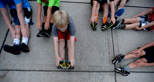 Hudson Oakes stretches with a group of runners as they train with certified running coach Mandy Oakes on Wednesday, August 22, 2018, in Franklin, Tenn., for the upcoming Franklin Classic.