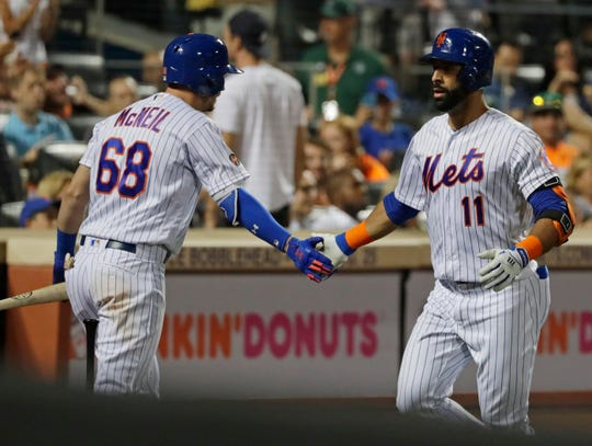 New York Mets' Jose Bautista (11) celebrates with teammate Jeff McNeil (68) after hitting a home run during the fourth inning of a baseball game against the San Francisco Giants non Wednesday, Aug. 22, 2018, in New York.