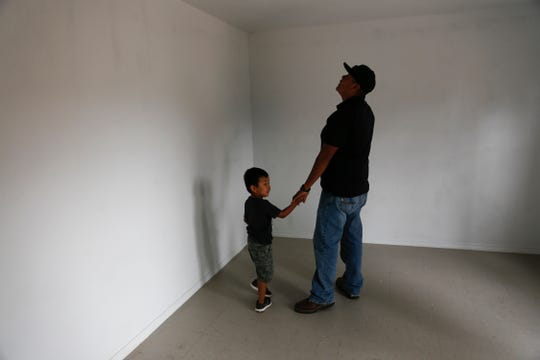 Ethann Becenti and his father Brandon Becenti explore a rebuilt home Tuesday in Ch'ooshgai Mountain's Naschitti Chapter area.