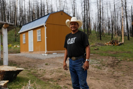 Jerone Willetto poses next to his rebuilt home Tuesday in Ch'ooshgai Mountain's Naschitti Chapter area.