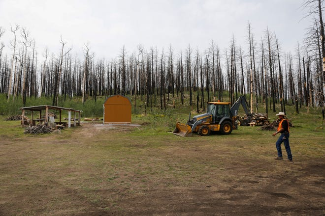 Jerone Willeto walks toward his new home Tuesday in Ch'ooshgai Mountain's Naschitti Chapter area. Burned trees from the 2014 Asaayii Lake Fire are seen in the background.