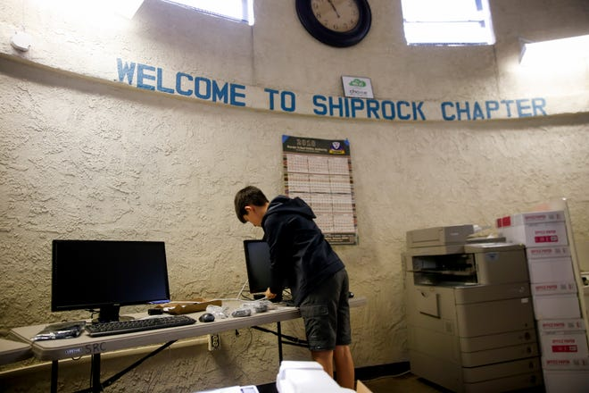 GreenBridge Computing Inc. intern James Yunger sets up computers Thursday at the Shiprock Chapter house.