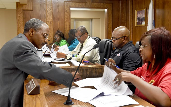 City auditor Stephen Woods hands information on Tuesday night to Opelousas Board of Alderman Budget Committee chairperson Jacqueline Martin during a special meeting.