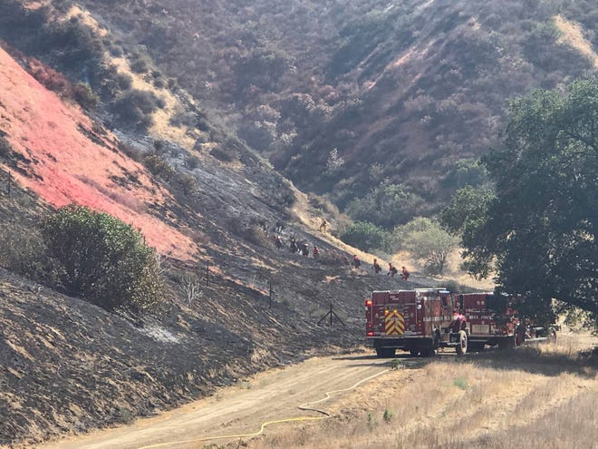 Firefighters working to control the Land Fire climb steep terrain where red fire retardant  was dropped from helicopters overhead Wednesday near Highway 60 in Beaumont.