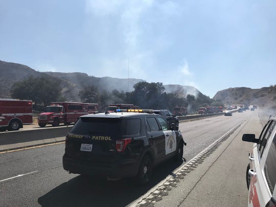 California Highway Patrol along Highway 60 Wednesday shortly before shutting down the freeway as a wildfire burned a short distance away.