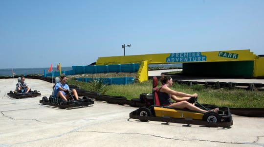 Ohio tourists Makenna Babo and Chase Cole enjoy their vacation Thursday with a trip to Premier Adventure Park on Pensacola Beach.