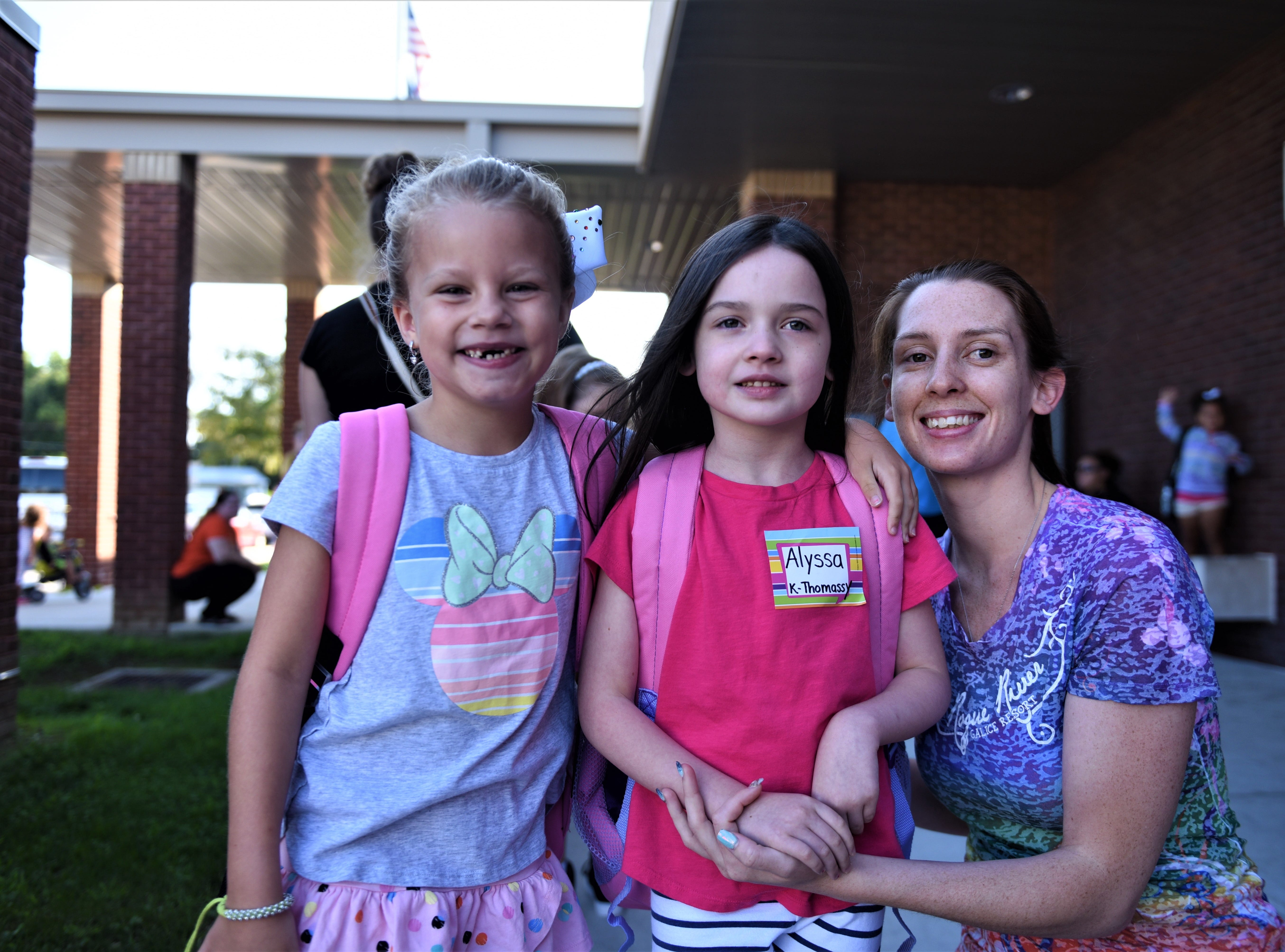 Alyssa Wonder is sent off for her first day of kindergarten by her mom. With her, on the left, is Ariel Garver starting her first day of second grade.