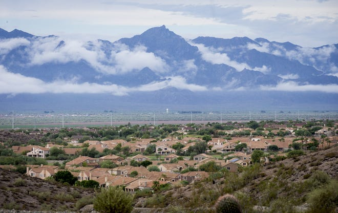The Estrella Mountains are shrouded in clouds following Wednesday morning's monsoon showers. Photo shot from Ahwautukee, Aug. 13, 2014.