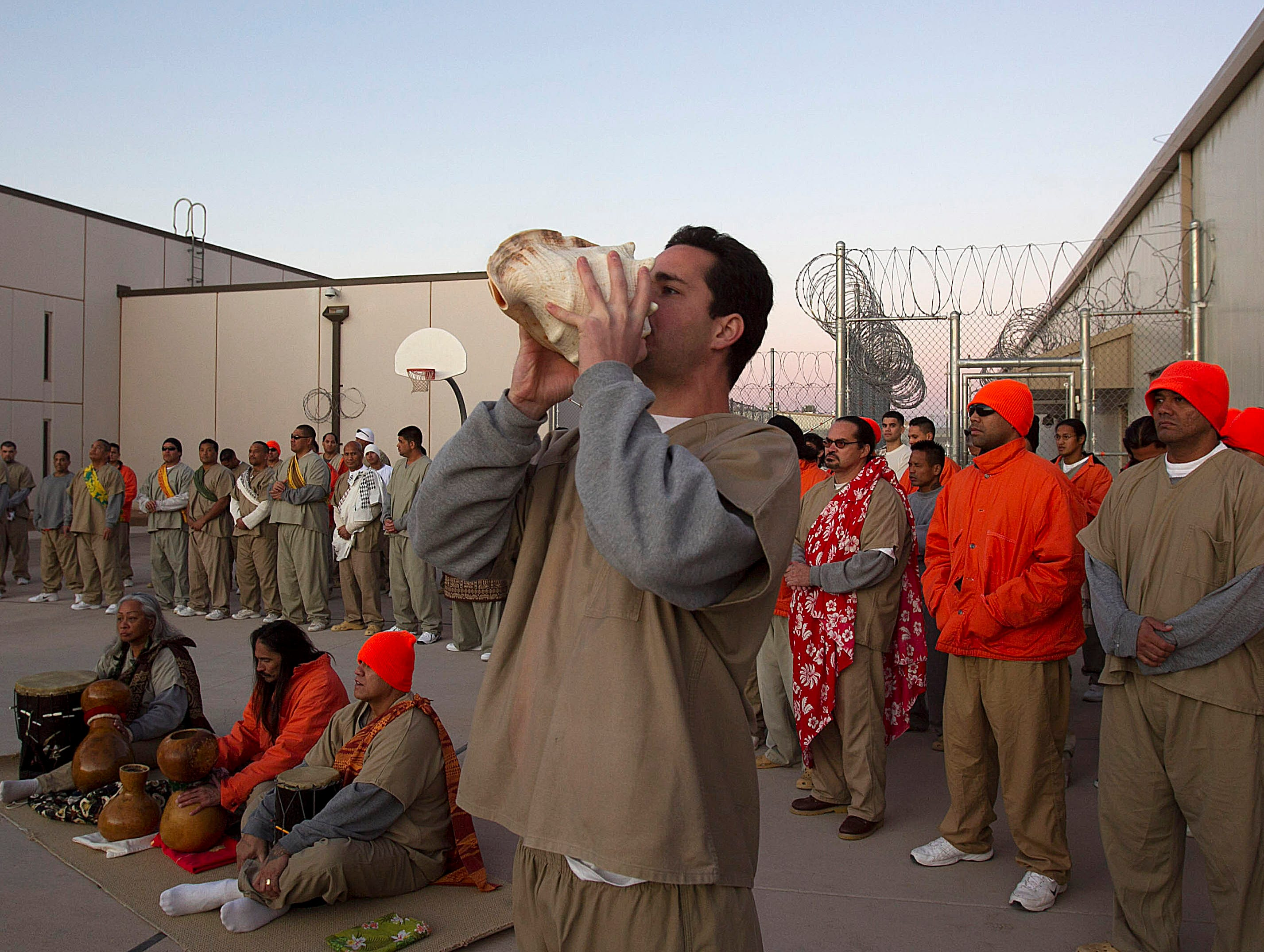Leeloy Kekupono blows a conch shell during Hawaiian inmates' prayers for the beginning of the Makahiki season of harvest and a sunrise service at Saguaro Correctional Center in Eloy on Oct. 9, 2011.