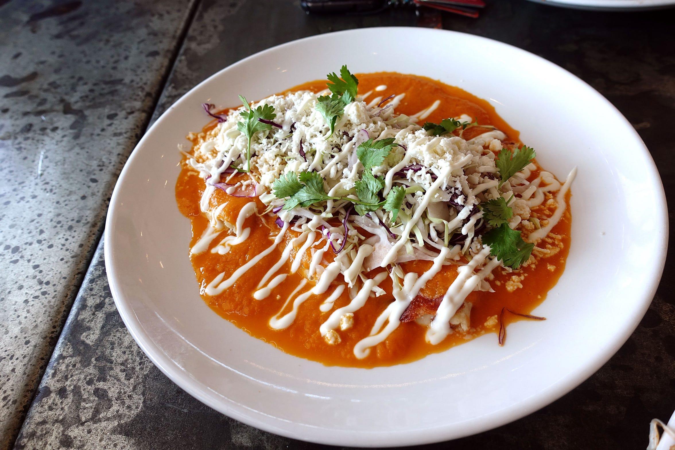 Entomatadas with corn tortillas, asadero cheese, cabbage, crema fresca, queso fresco and cilantro at Roland's Cafe Market Bar.