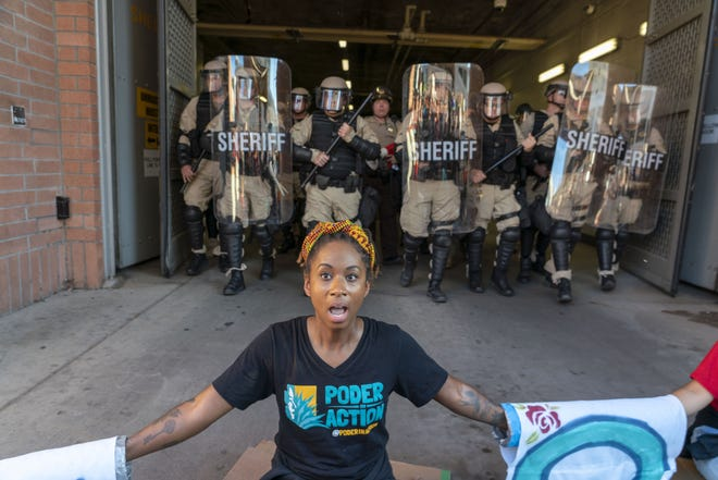 Parris Wallace, 32, from Poder in Action gets arrested during a protest by the Puente Human Rights Movement outside 4th Ave Jail on Aug. 22, 2018.
